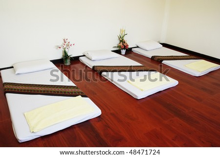 Spa and massage bed with some decorations. - stock photo