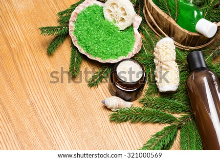 Spa and pampering products and accessories: sea salt in shell, loofah, wisp of bast, skin care cream, shampoo and shower gel in wooden basket surrounded by fir branches. Copy space - stock photo