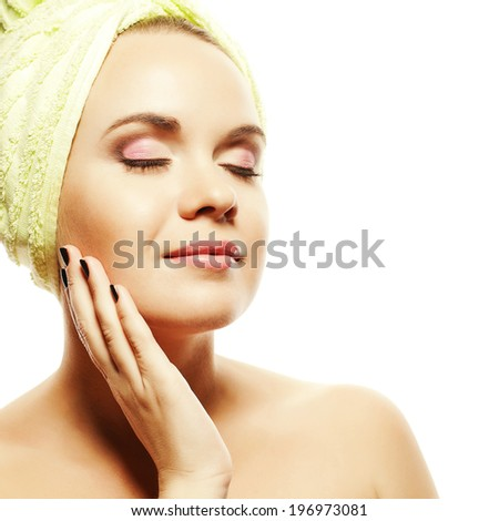 Spa and skincare concept. Portrait of beautiful girl with with light green towel on head and touching face. Closed eyes. Perfect skin and make-up. Copy-space. Close up. Studio Shot