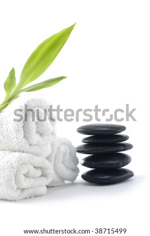 spa and wellness concept with rolled towel, hot stones with bamboo - stock photo