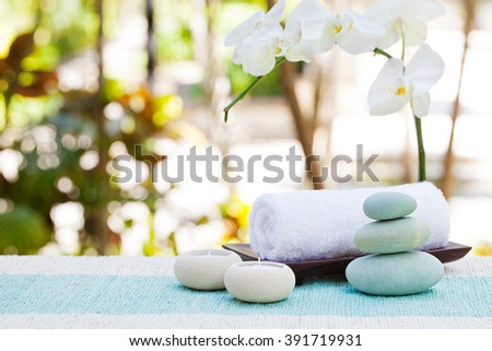 Spa and wellness massage setting Still life with candle, towel and stones Outdoor summer background with fresh white orchid Copy space - stock photo