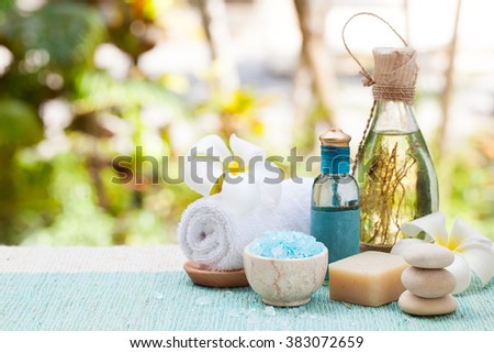 Spa and wellness massage setting Still life with essential oil, salt and stones Outdoor summer background Copy space - stock photo