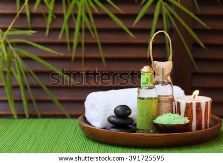 Spa and wellness massage setting Still life with essential oil, salt, stones and cinnamon candle Wooden background with bamboo leaves. Copy space - stock photo