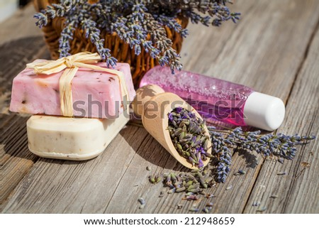 Spa and wellness setting. Natural handmade lavender oil and soap and fresh lavender flowers on wooden background - stock photo