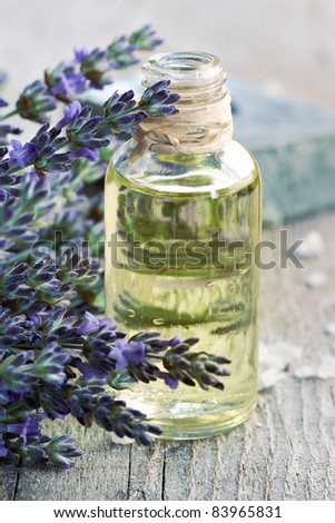 Spa and wellness setting. Natural handmade lavender oil and soap with bath salt and fresh lavender on wooden background - stock photo