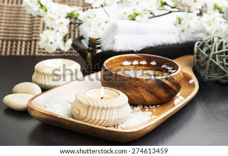 Spa and Wellness Setting with Candle, Water Bowl and Spring Flower Blossom Branch in the Background - stock photo