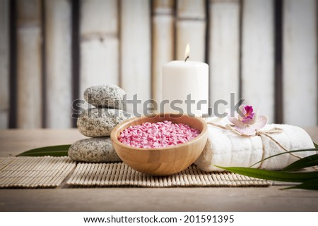 Spa and wellness setting with flowers, candles and towel - stock photo