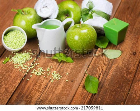 Spa and wellness setting with green apples, bath salt, aromatic candle on wooden background  - stock photo