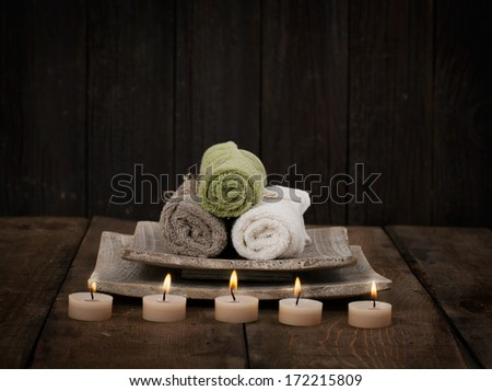Spa and wellness setting with natural soap, candles and towel. Wooden dayspa nature setting - stock photo