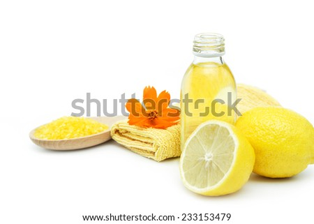 Spa and wellness setting with sea salt, oil essence, flowers and towels isolated. Relax and treatment therapy. White background. Selective focus on a bottle. Close up. - stock photo