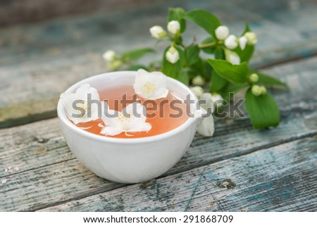Spa and wellness setting with sea salt, oil essence, jasmin flowers and towels on wooden background.  Relax and treatment therapy. space for text.  Selective focus. Close up. - stock photo