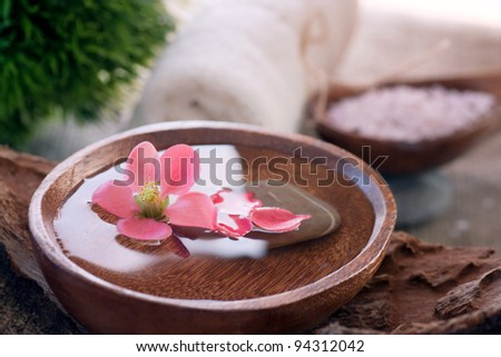 Spa and wellness  setting with water for treatment and flowers. - stock photo