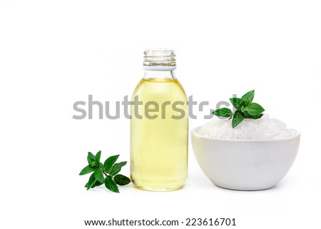 Spa and wellness setting with white sea salt, oil essence and mint on white background. Manicure, relax and treatment therapy. Selective focus. Close up. - stock photo