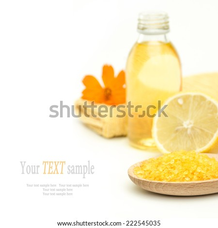 Spa and wellness setting yellow sea salt, oil essence and lemon on white background.  Selective focus on sea salt. Manicure set, relax and treatment therapy. Close up. - stock photo