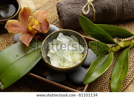 Spa aroma bowl of salt and orchid with towel and green leaves on mat - stock photo