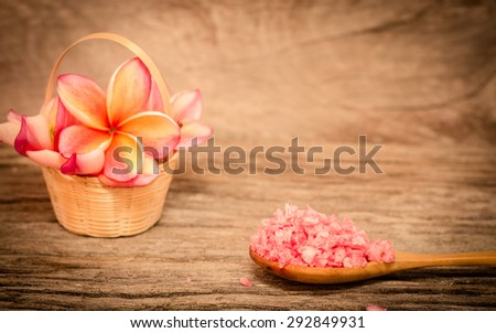 Spa & aromatherapy concept,Red and white frangipani flower with spa salt on wooden background in the vintage style. - stock photo