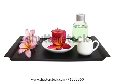 Spa & aromatherapy set including aromatherapy candle, perfumes, milk/oil jar and frangipani flowers - stock photo