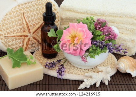 Spa arrangement of herb and flower leaf sprigs, cream towels, exfoliating  scrub, aromatherapy essential oil bottle, sea coral and natural soap over bamboo. - stock photo