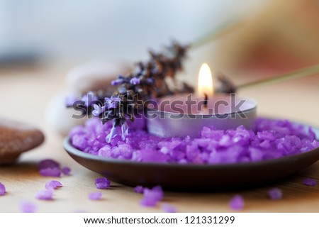 Spa background, candle in a saucer with salt baths and sprigs of lavender - stock photo