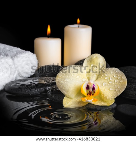 spa background of yellow orchid (phalaenopsis) on zen stones, drops, candles and stacked of towels with ripple reflection water, close up - stock photo