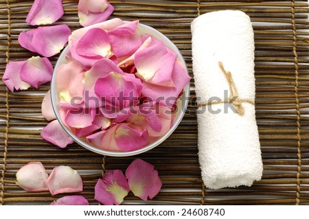 Spa background -Rose petal floating in water in bowl with towel - stock photo