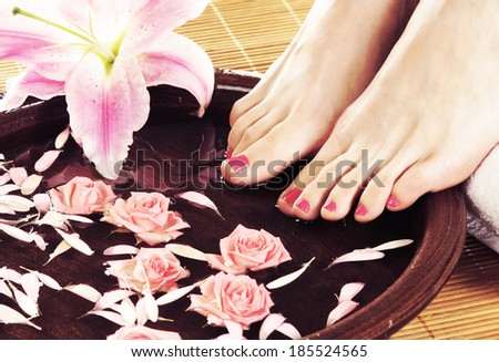 Spa background with a Beautiful female legs with a lily flower - stock photo