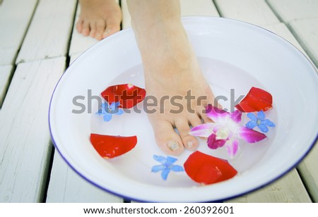 Spa background with a beautiful legs, flowers, petals and ceramic bowl - stock photo
