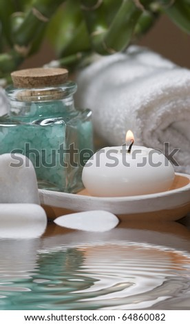 Spa background with bath salts, a towel, a candle and bamboo plants. - stock photo