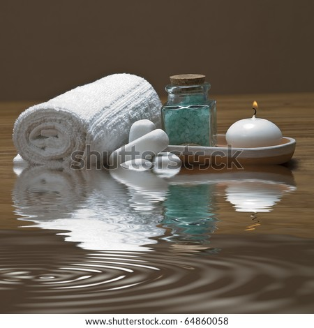 Spa background with bath salts, a towel  and a  candle reflected on water.