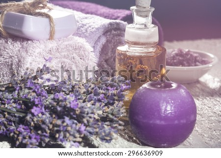 Spa background with bunch of lavender, towel, sea salt, candles and bottles with aromatherapy oil on a white wooden background. With special blurred effect. - stock photo