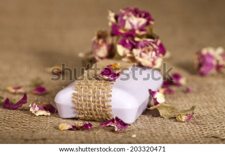 Spa background with purple soap and dried roses on burlap texture. Selective focus. - stock photo