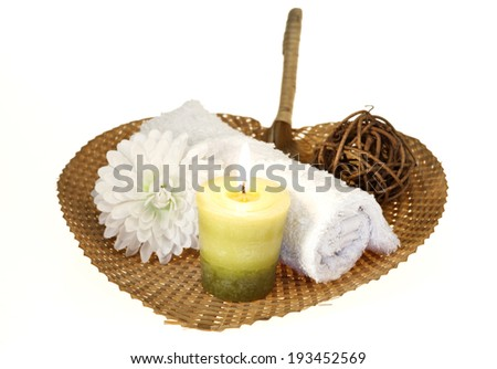 Spa background with rolled towel and green candle with flower on a pad.