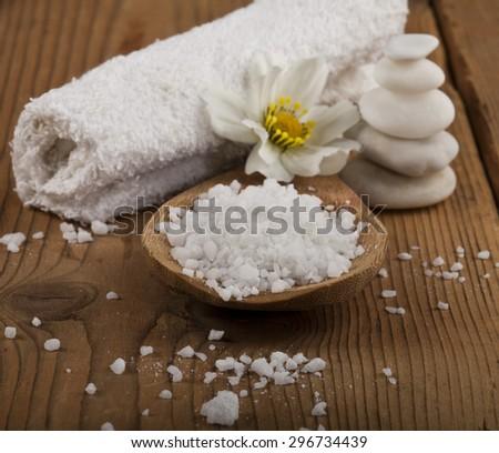 Spa background with sea salt in wooden spoon, rolled towel, white stones and flower. - stock photo