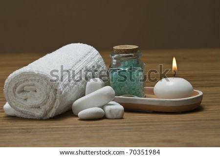 Spa background with  towels, candles and bath salts in green. - stock photo
