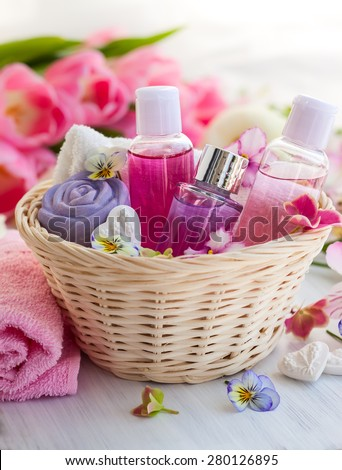 Spa bath toiletries set in basket with fresh flowers - stock photo