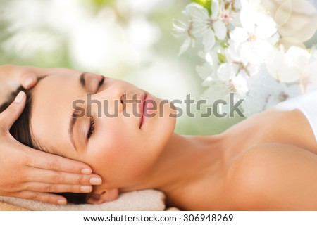 spa, beauty, people and body care concept - beautiful woman getting face treatment over green natural background - stock photo