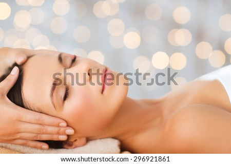 spa, beauty, people and body care concept - beautiful woman getting face treatment over holidays lights background - stock photo