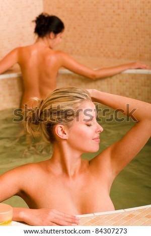 Spa beauty relax pool two naked women inside water healthy - stock photo
