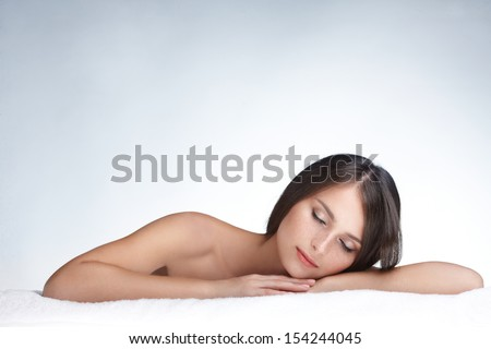 Spa beauty skin treatment woman on white towel. model with perfect skin lying on towel. On white background