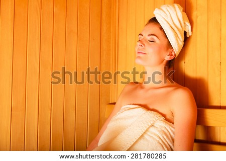 Spa beauty treatment and relaxation concept. Woman white towel relaxing in wooden sauna room. - stock photo
