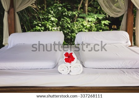 Spa bungalow, inner view. White bed and white towels with exotic flower - stock photo