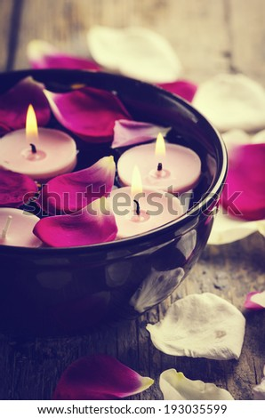 Spa candles and rose petals. retro filter. - stock photo