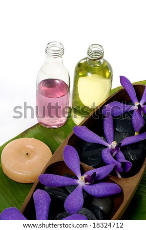 spa collection of aroma oils, flower and black pebbles