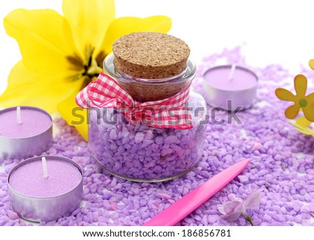 spa composition of candles, bottle and flowers