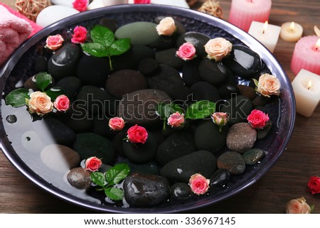 Spa composition of candles, flowers and stones in water, close-up