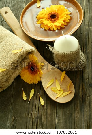 spa composition of gerber flowers, candle and towel on old wooden boards - stock photo