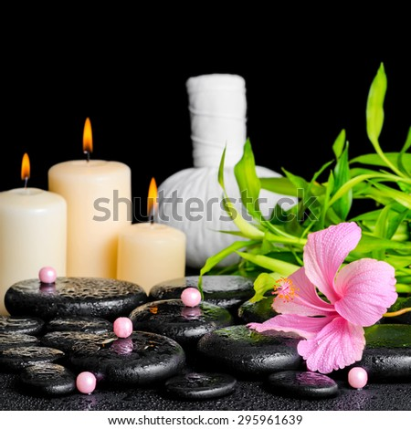 spa composition of hibiscus flower, bamboo, thai herbal compress ball, beads and candles on zen basalt stones with drops, closeup - stock photo