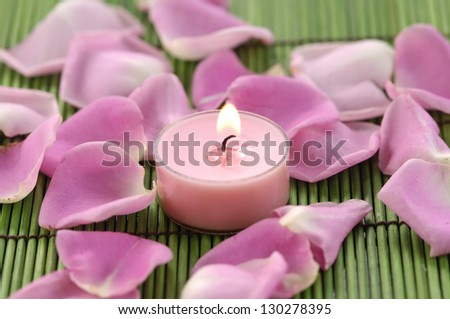 Spa composition of rose petals and candle on green mat