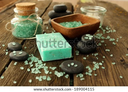 spa composition of soap, bath salt and stones on old wooden boards
