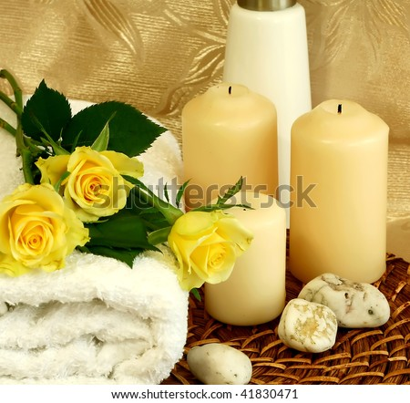 spa composition of towel, candles and yellow roses